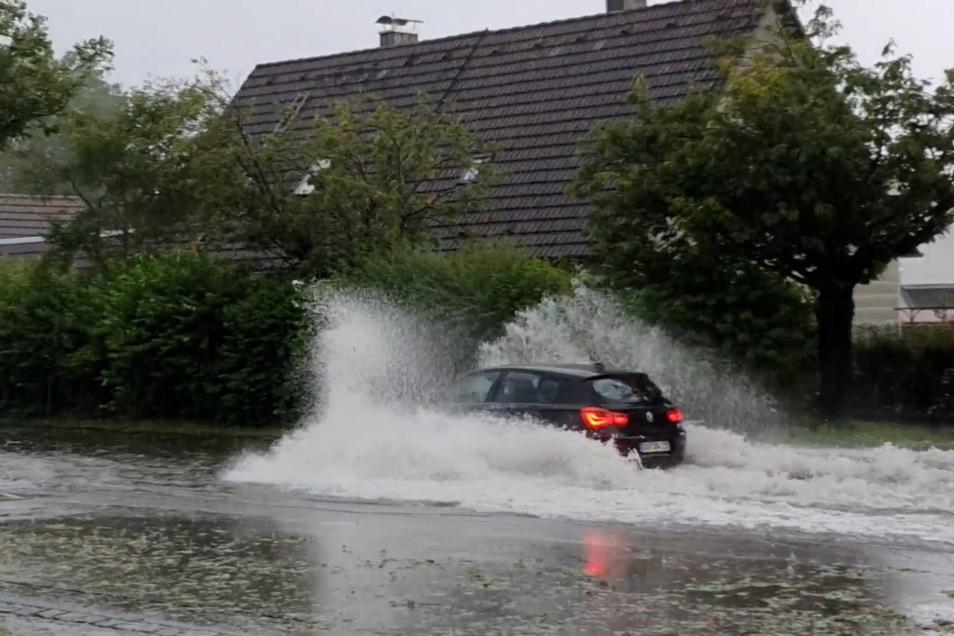 25.07.2021, Bayern, Penzberg: Ein Auto fährt durch das stehende Wasser auf einer Straße im Ort und schiebt eine Bugwelle vor sich her. In Teilen Bayerns gab es am Sonntag heftige Unwetter.