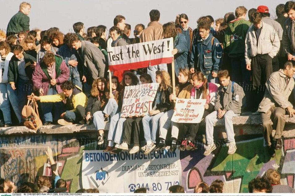Menschen auf der Berliner Mauer in den Tagen des Mauerfalls 1989. Ob sie damals geahnt haben, wie lange die Wiedervereinigung von Ost und West dauern wird?