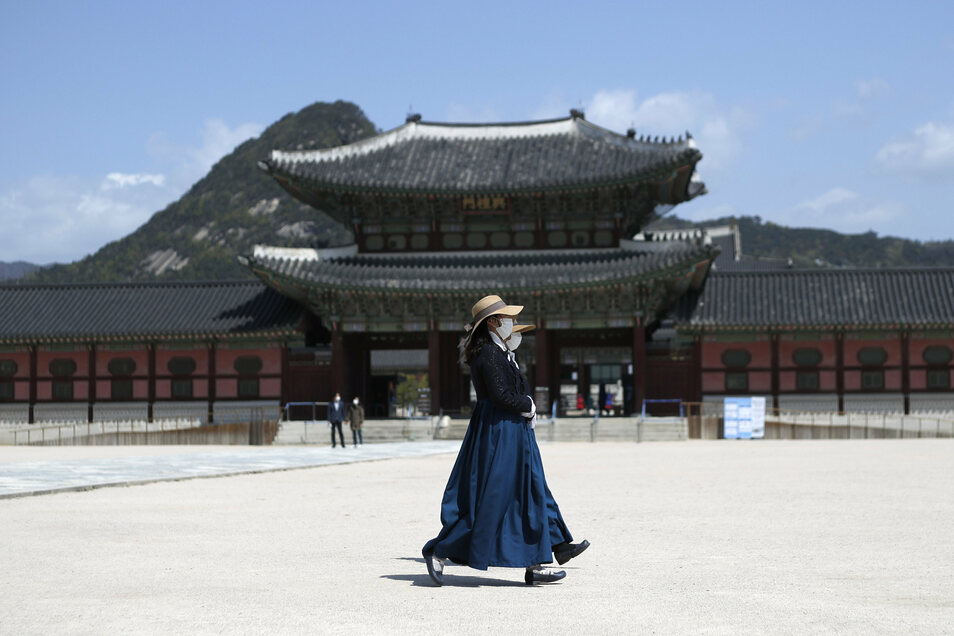 Frauen mit Mundschutz gehen am Gyeongbokgung Palast in Seoul vorbei. In Südkorea ist ein Ende der Corona-Pandemie absehbar.