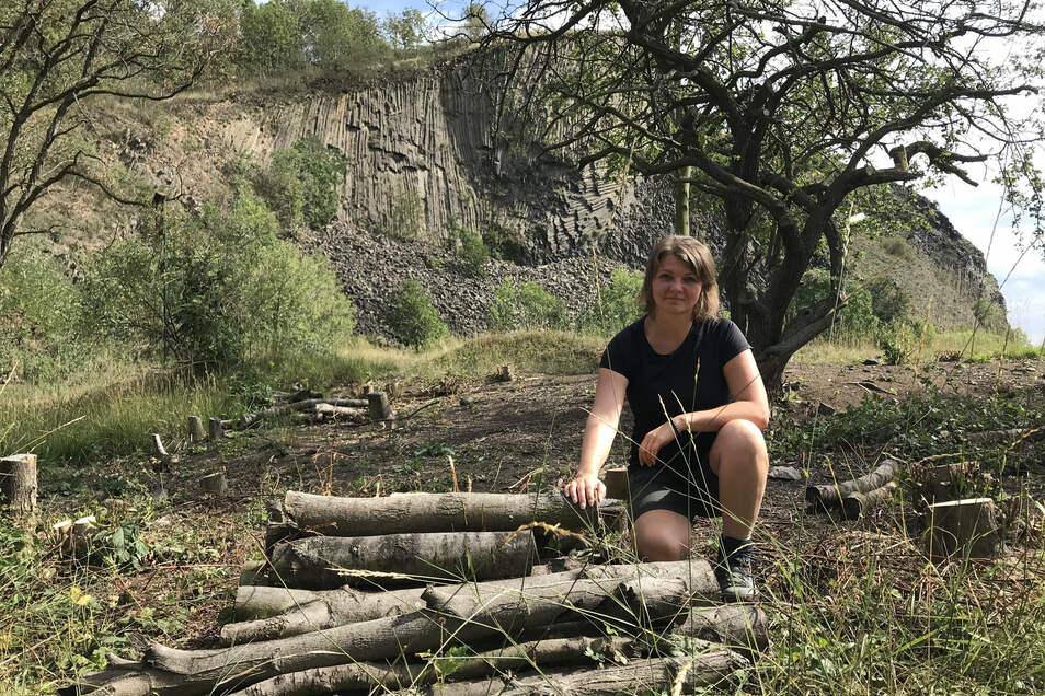 Lucie Benešová zeigt einen Stapel aus Robinienstämmen. Deren Reste werden als Lebensraum für Insekten genutzt.