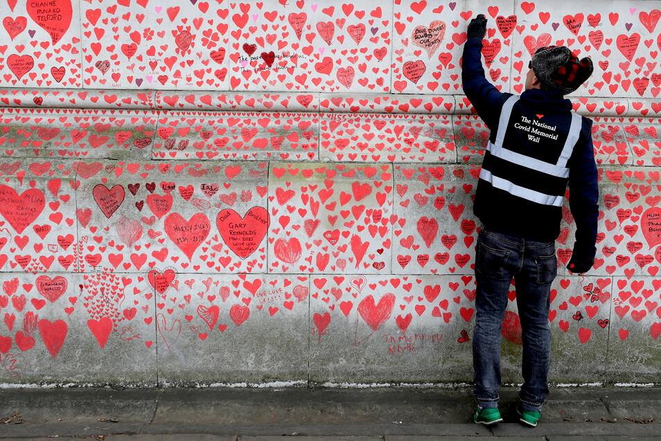 Ein Mann malt gegenüber dem britischen Parlament ein rotes Herz neben andere Herzen auf eine Gedenkmauer, die an die Opfer der Corona-Pandemie erinnern soll.