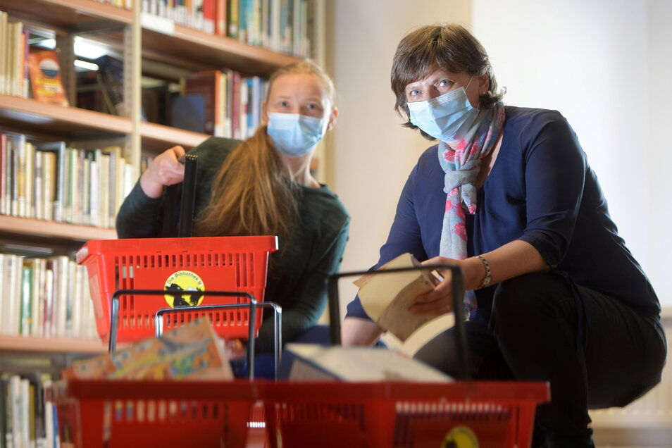 Carola Becker (r.) und Viktoria Stabrey von der Christian-Weise-Bibliothek Zittau füllen die Körbe mit bestellten Büchern und Spielen. Ab Montag dürfen Besucher auch wieder hinein.
