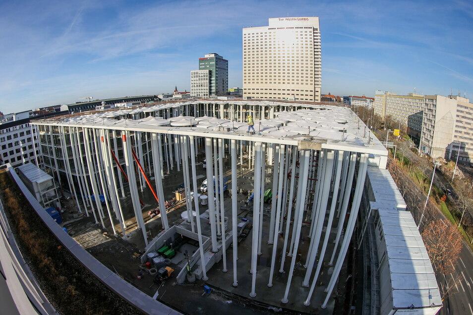 Bauarbeiter errichten den Säulengarten vor dem Neubau der SAB in Leipzig. Das Bauwerk sollte ursprünglich 2019 fertig sein, die Insolvenz des Generalplaners verzögerte das Projekt.