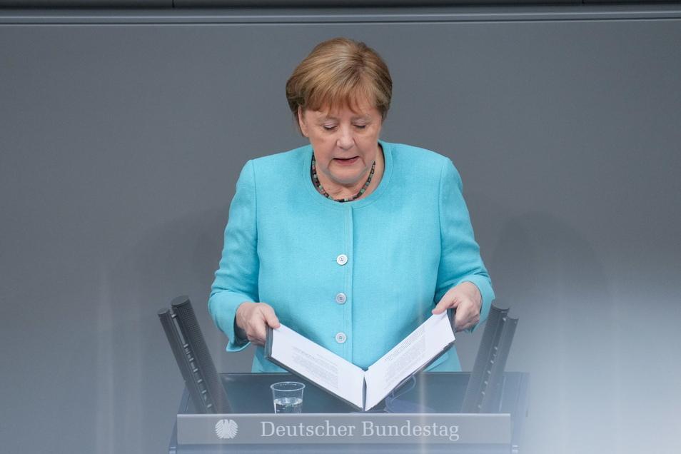 Bundeskanzlerin Angela Merkel (CDU) klappt nach der Regierungserklärung zum bevorstehenden EU-Gipfel bei der Sitzung des Deutschen Bundestags das Redemanuskript zu.