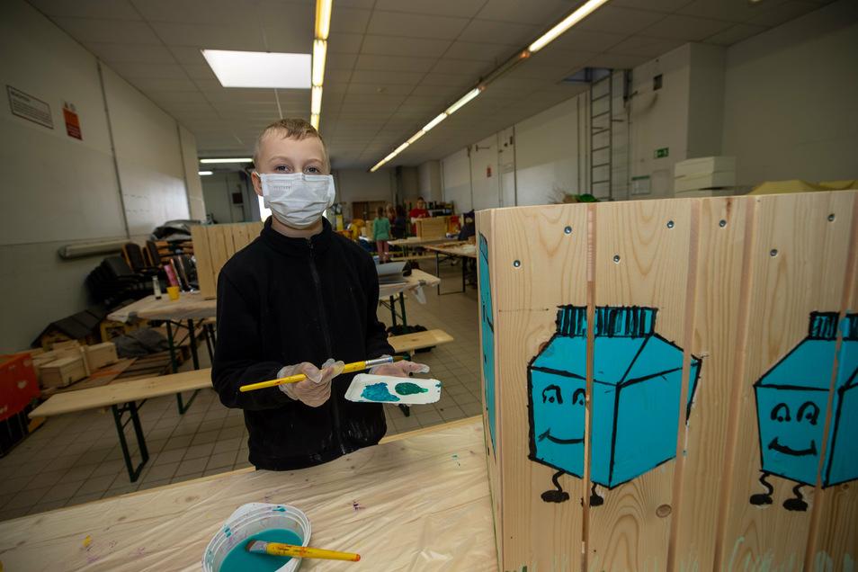 Elias steht mit Farbe und Pinsel vor seiner gestalteten Mülleimerverkleidung auf dem eine Schutzverpackung für Lebensmittel zusehen ist.