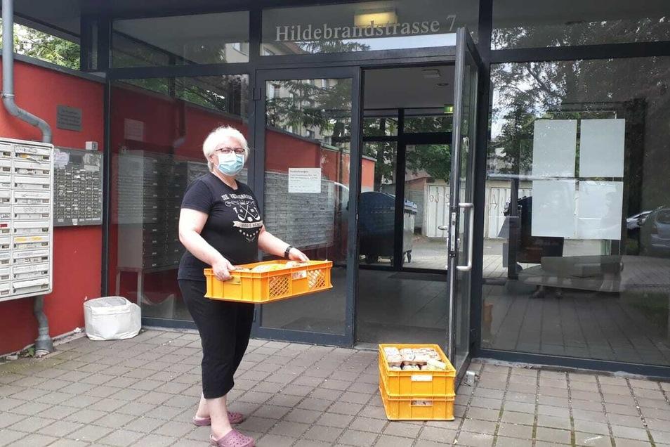 Rosi Scharf von der Heilsarmee trägt Kisten mit Lebensmitteln in das Wohnheim.