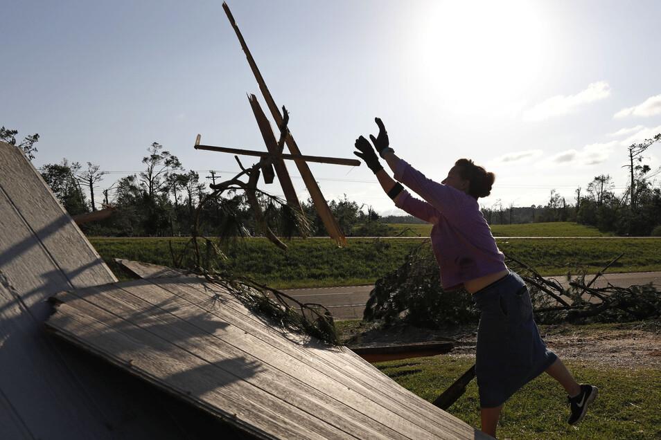 Eine Frau wirft Holz auf einen Stapel, während sie mit Familie und Freunden die Überreste eines Hauses aufräumt.