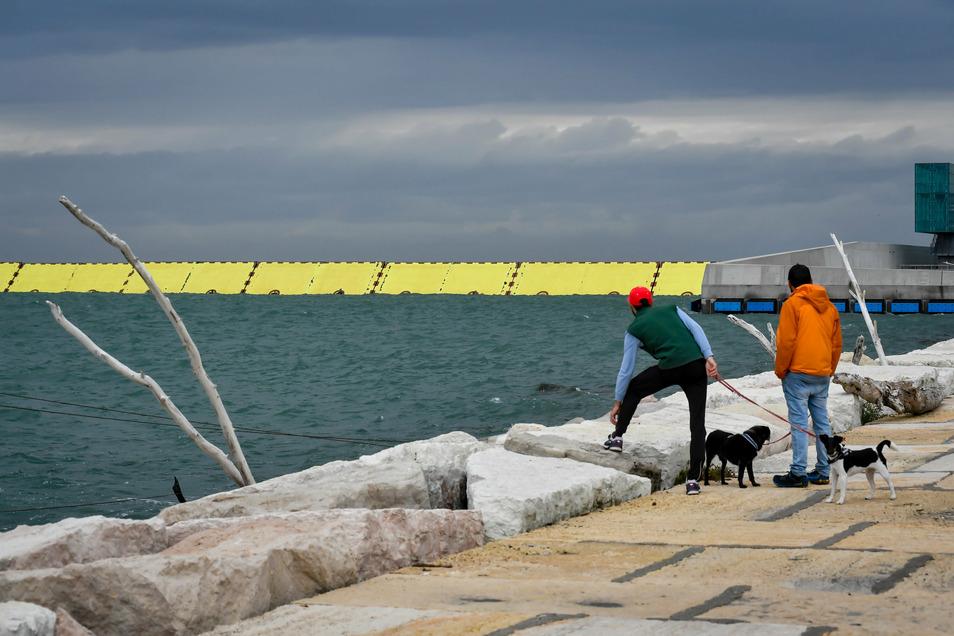 Zwei Passanten stehen am Wasser während die neue Hochwasserschutzanlage Mose vor Venedig erstmals zum Schutz vor Hochwasser hochgefahren wird.