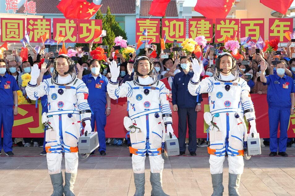 Die Astronauten Tang Hongbo (l-r), Liu Boming und Nie Haisheng winken während einer Verabschiedungszeremonie für die chinesischen Astronauten vor dem Start im Jiuquan Satellite Launch Center in Jiuquan im Nordwesten Chinas vorbereiten.