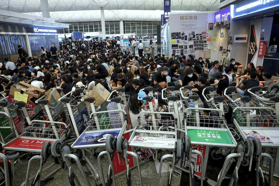 Demonstranten blockieren mit Gepäckwägen den Weg zu den Gates am Hongkonger Flughafen.