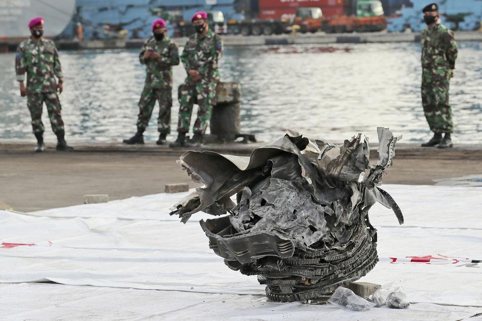 Marinesoldaten betrachten ein großes Teil eines Flugzeugs, das aus den Gewässern vor der Insel Java geborgen wurde.