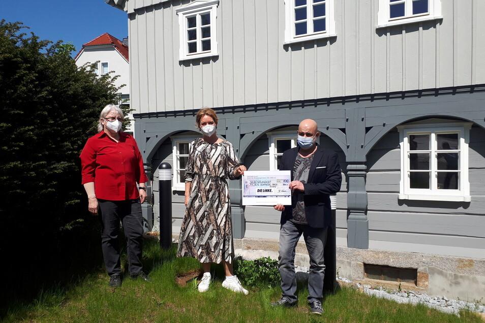 Sonja Wagner (l.)vom Förderverein Alte Schmiede und Thomas Polpitz (r.), Bürgermeister von Obergurig und Vorsitzender des Vereins, nahmen den Scheck von der Bundestagsabgeordneten Caren Lay (Die Linke) vor dem alten Schmiedegebäude in Obergurig entgegen.