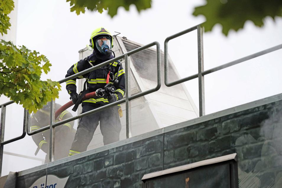 Franz Lupprian geht auf dem Dach des Brandübungscontainers mit dem Strahlrohr in der Hand zum ersten Ziel.