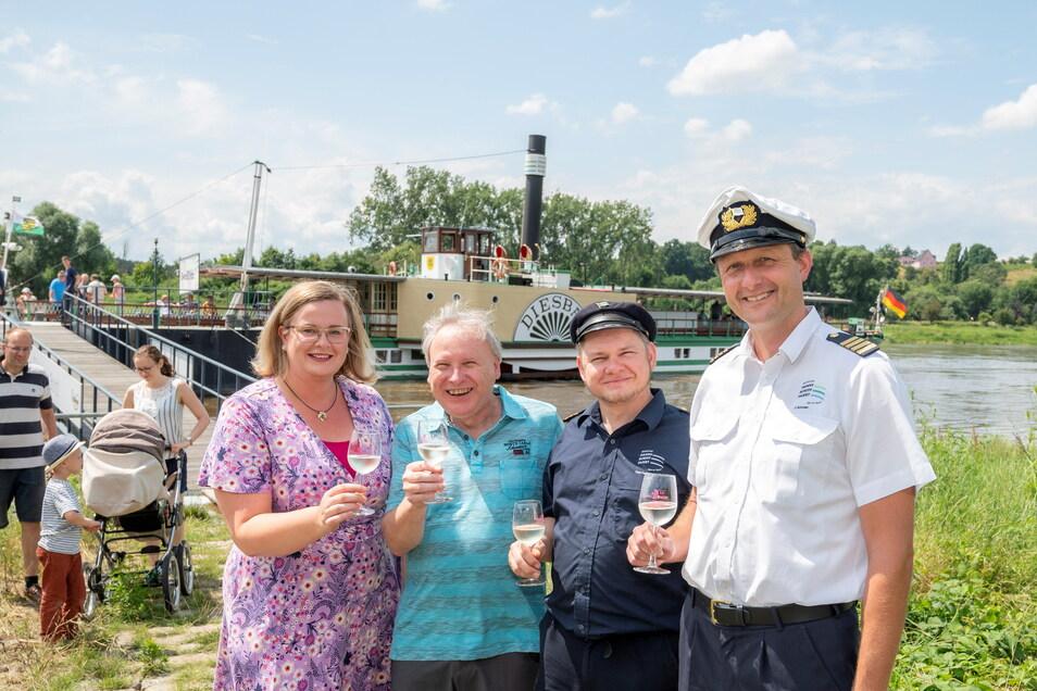 (V.l.n.r.) Die ehemalige sächsische Weinkönigin Maria Lehmann und Bürgermeister Gerd Barthold begrüßen Maschinist Falk Hering und Kapitän Jan Schröter an Land mit einem Glas Secco.