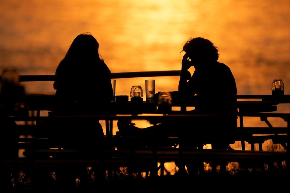Menschen genießen den Sonnenuntergang in einem Biergarten.
