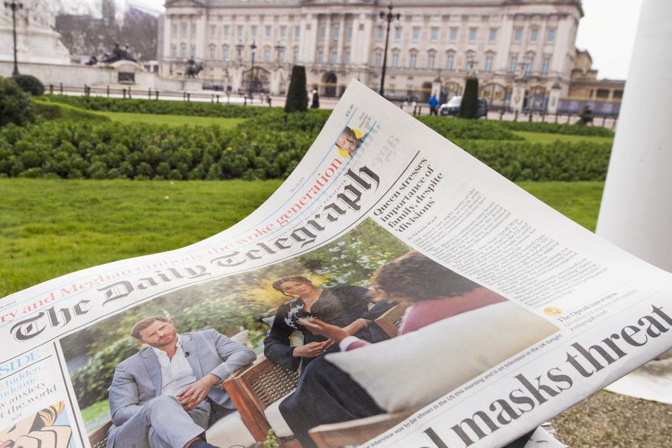 """Ein Ausschnitt aus dem Interview von US-Moderatorin Winfrey mit Prinz Harry und Herzogin Meghan ist auf der Titelseite des """"The Daily Telegraph"""" abgedruckt. Im Hintergrund ist der Buckingham Palace zu sehen."""