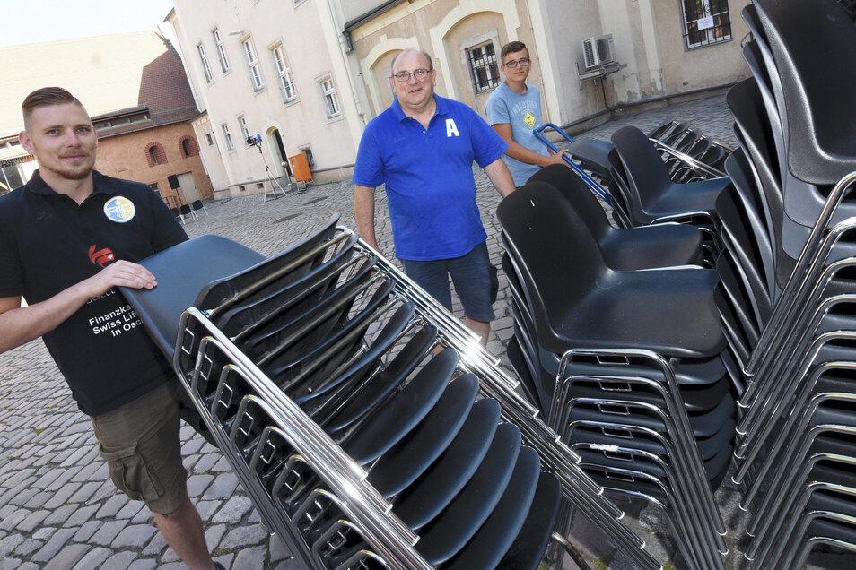 Lucas Schröber, Andreas Rost und Leon Malchau (v.l.) vom HSG Rio stellen am Donnerstagabend die Stühle für die Sommerbühne im Klosterhof Riesa auf. Etwa 300 Sitzmöbel müssen bei jeder Veranstaltung verteilt werden.