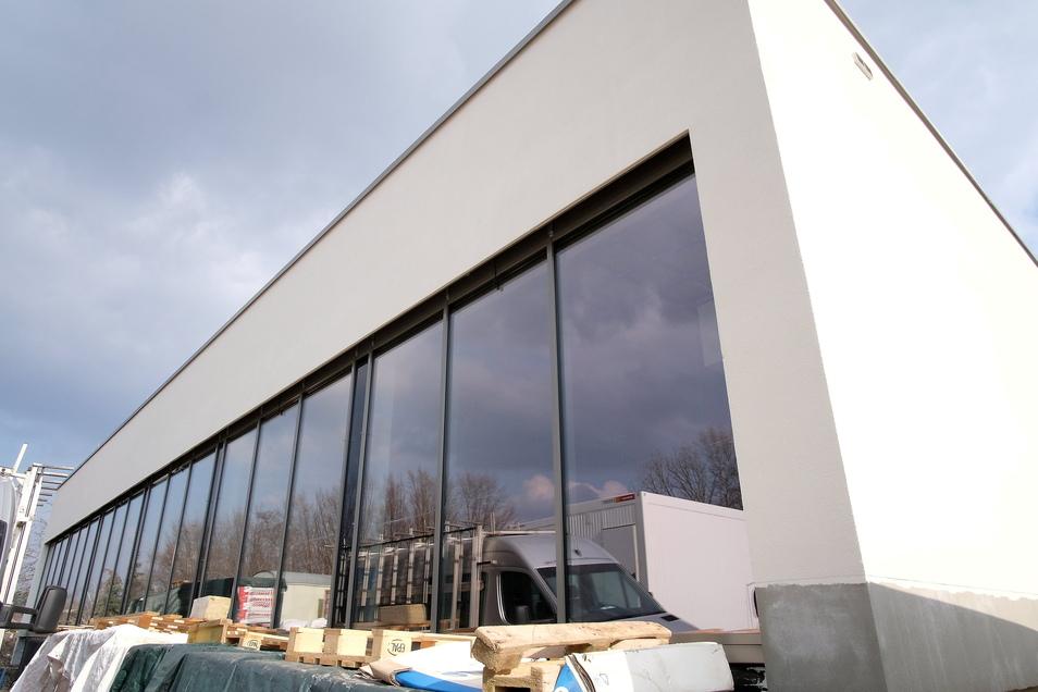 Von außen fertig: Die neue Sporthalle der Questenberggrundschule hebt sich hell gegen den dunklen Himmel über Meißen ab. Auch sonst geht es auf der Großbaustelle zügig voran.