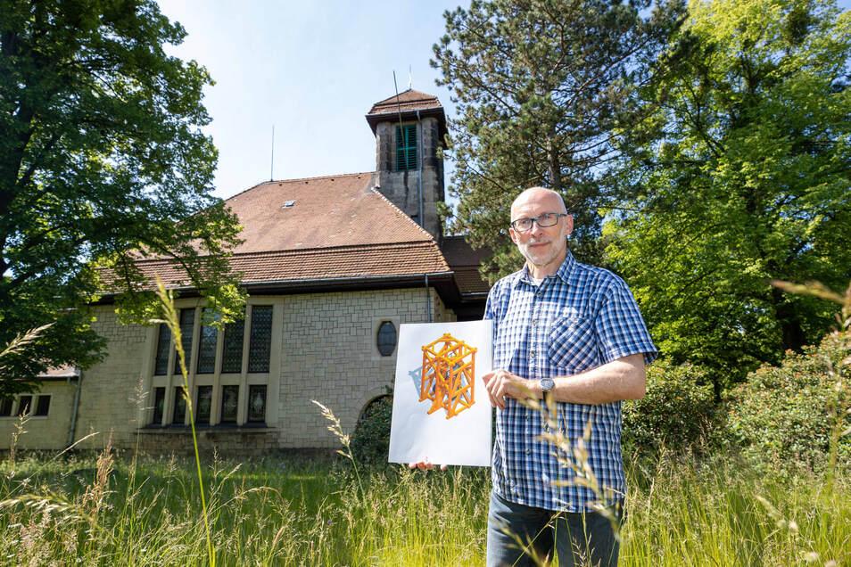 Pfarrer Burkhard Nitzsche steht auf einer Wiese mit der Graupaer Kirche im Hintergrund. In der Hand hat er eine Zeichnung des neuen Glockenstuhls.