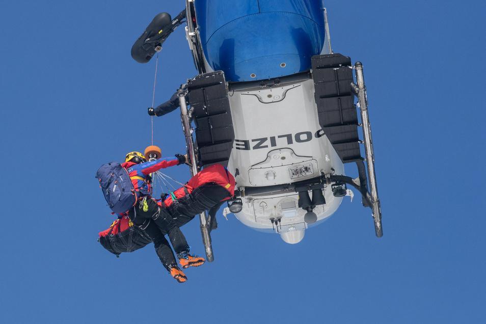 Ein Mitglied der Bergwacht und eine aus dem Schnee gerettete Person werden bei einer Lawinenübung des Alpinen Einsatzzuges der Polizei und Bergwacht in einen Polizeihubschrauber gezogen.