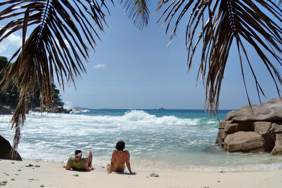Touristen liegen am Strand auf der Insel La Digue - sie gehört zu den Seychellen im Indischen Ozean vor der Küste Ostafrikas.