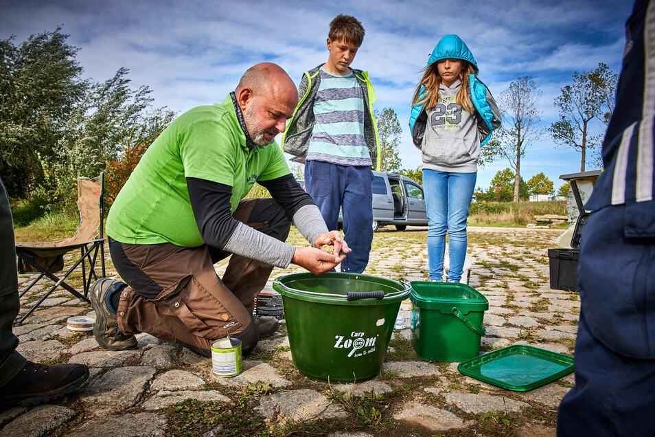 Lehrstunde am Strand: Jugendwart Jens Langwisch zeigt den Kindern, wie man Futterklopse zum Anlocken der Fische zubereitet.