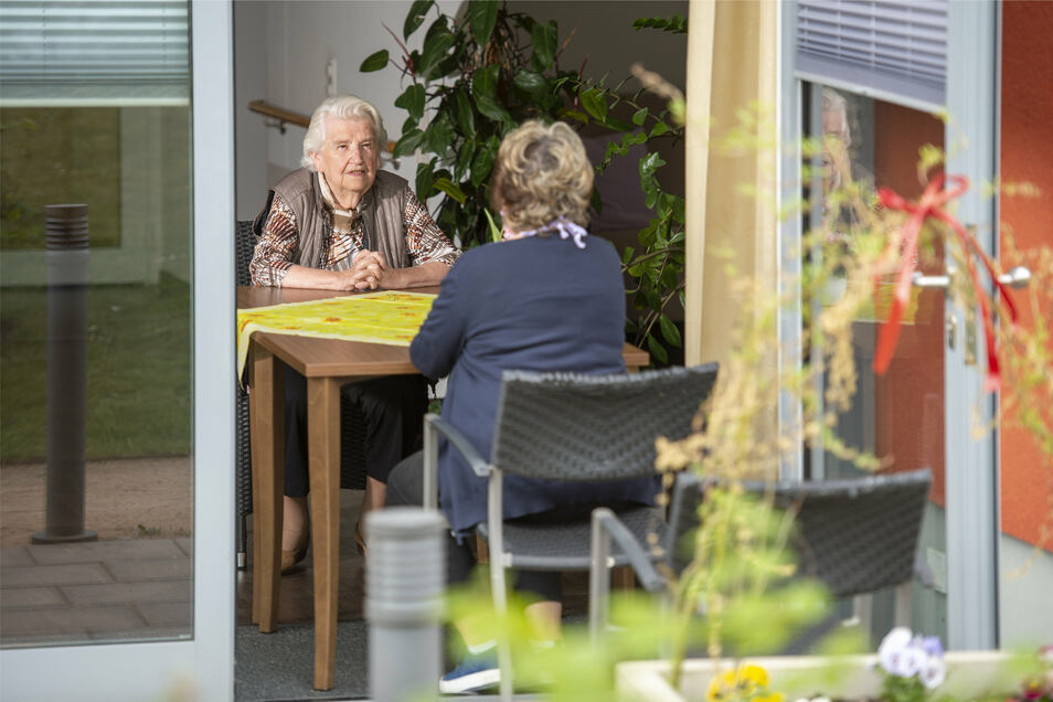 Bewohnerin Charlotte Jahn (l.) empfängt an der Terrassentür des ASB Seniorenzentrums Am Schlossberg in Pirna mit dem nötigen Abstand eine Familienangehörige.