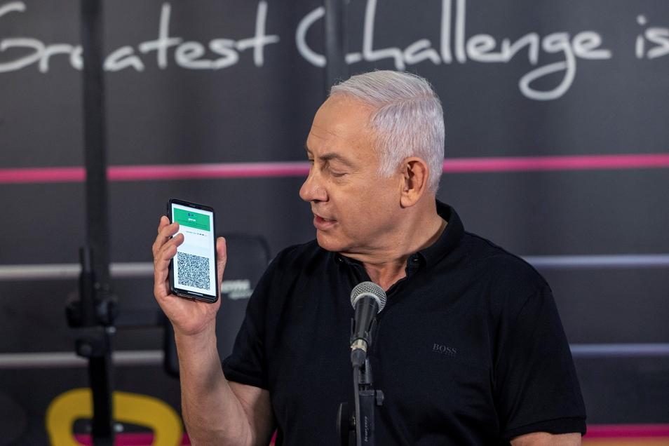 Benjamin Netanjahu, Ministerpräsident von Israel, spricht bei einer Pressekonferenz in einem Fitnessstudio vor der Wiedereröffnung der Filiale Petach Tikwa und hält ein Smartphone in der Hand mit der geöffneten App des Grünen Impfpasses.