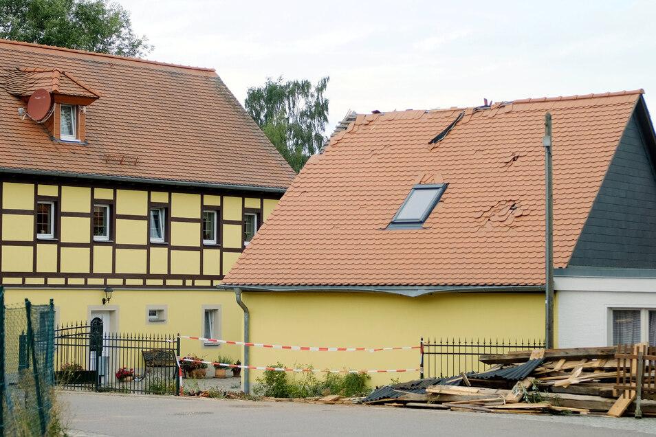 Das Schutzdach des einsturzgefährdeten Gebäudes hinter der Garage wurde von einer Windhose abgehoben, beschädigte dabei ein anderes Dach und landete auf der Straße.