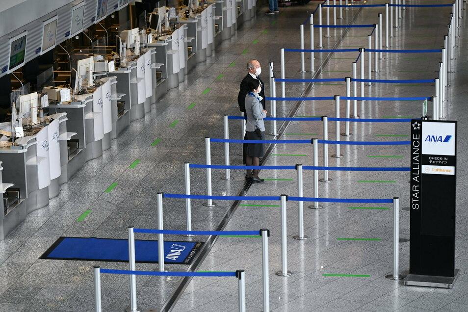 Mitarbeiter der Fluggesellschaft ANA stehen im Terminal 1 des Frankfurter Flughafens vor den leeren Abflugschaltern. Corona hat die Zahl der Passagiere an den deutschen Flughäfen auf den niedrigsten Stand seit der Wiedervereinigung gedrückt.