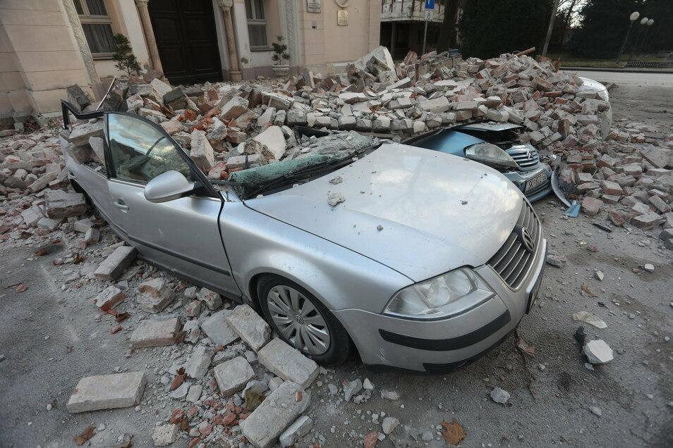 Kroatien, Sisak: Trümmer eines eingestürzten Hauses bedecken Fahrzeuge, die an einer Straße stehen. Ein Erdbeben der Stärke 6,4 hat erneut die kroatische Zentralregion erschüttert.
