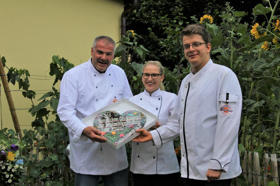Jessica Dörner hat erfolgreich ihre Kochlehre in der Pulsnitzer Genusswerkstatt abgeschlossen. Chef Armin Schumann (l.) und Pfefferküchlermeister Martin Kotzsch schenken ihr zum Abschied ein Pfefferkuchenherz.