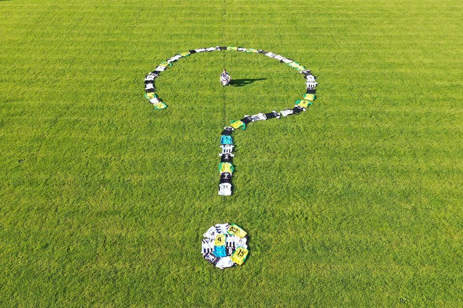Wie geht's mit dem Fußball? Ein Fragezeichen aus Trikots und Hosen steht symbolisch dafür.