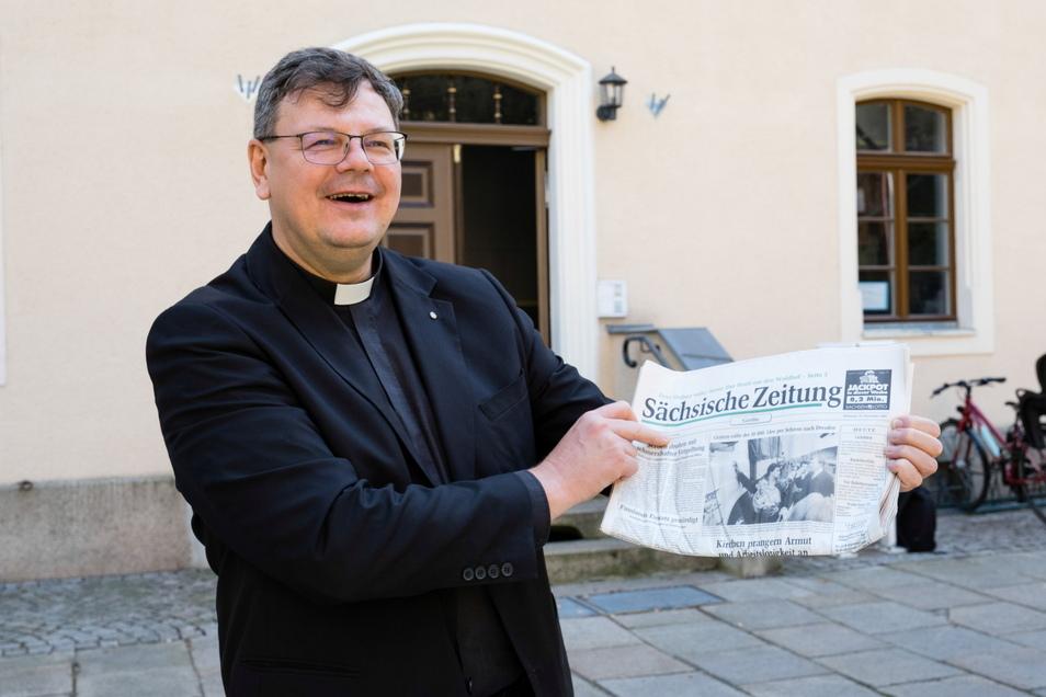 Pfarrer Roland Elsner mit einer Sächsischen Zeitung vom November 1993.