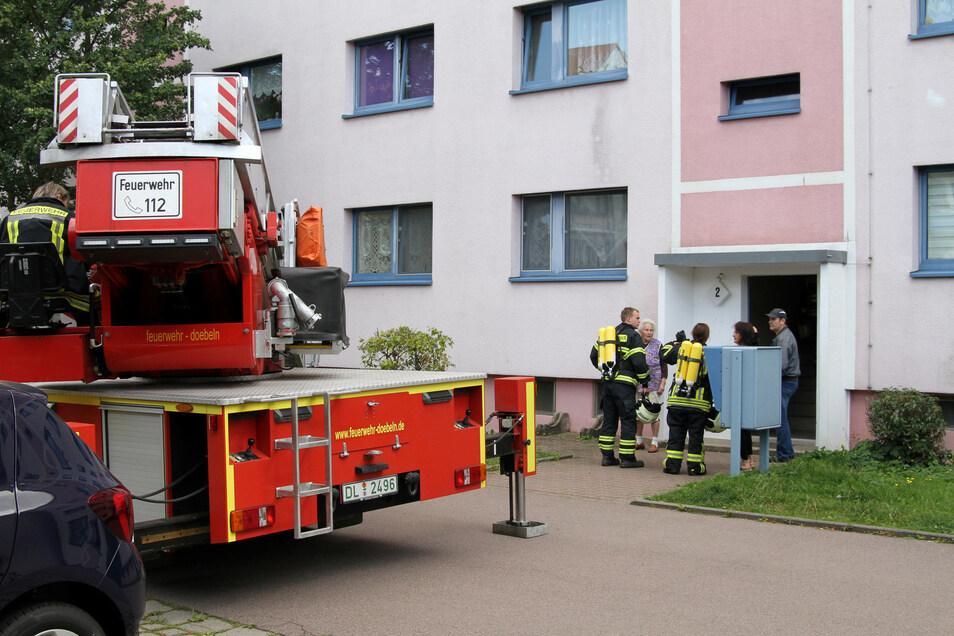 Kameraden der Döbelner Feuerwehr fragen Anwohner nach einer möglichen Brandursache.