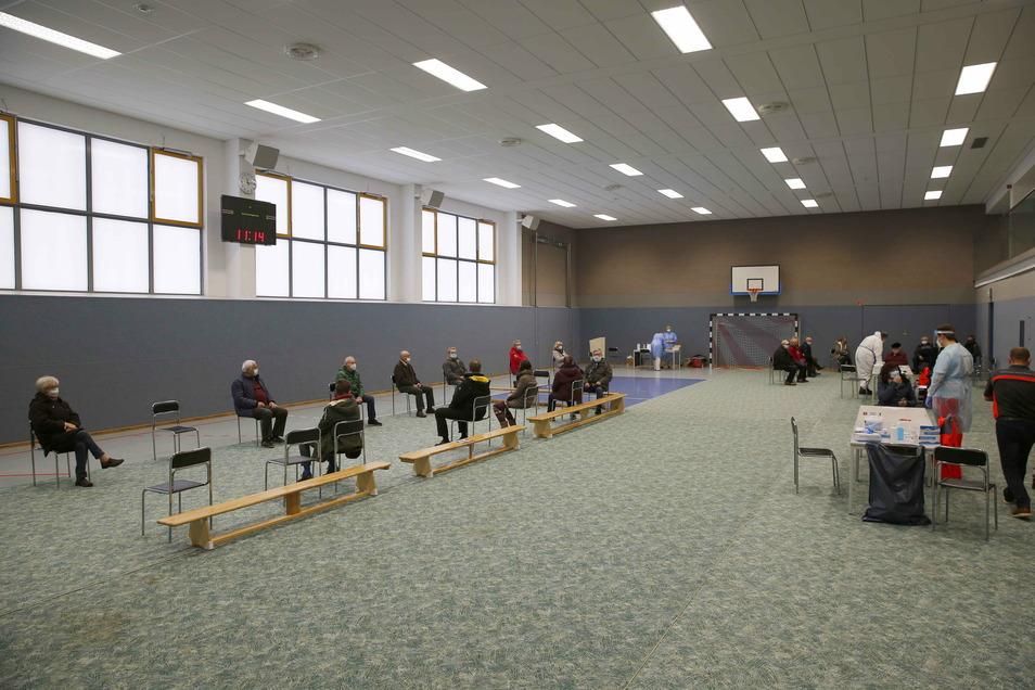 Links warten die Personen, die bereits getestet wurden, auf ihr Ergebnis. Es ist viel Platz in der Sporthalle von Räckelwitz.