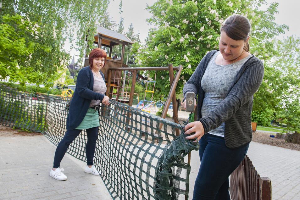 """Auf dem Gelände der Kita """"Sonnenschein"""" in Schönfeld stellen Leiterin Jana Hoyer (links) und ihre Stellvertreterin Anne Hansel Schneezäune auf, die die Kindergruppen auseinanderhalten sollen."""