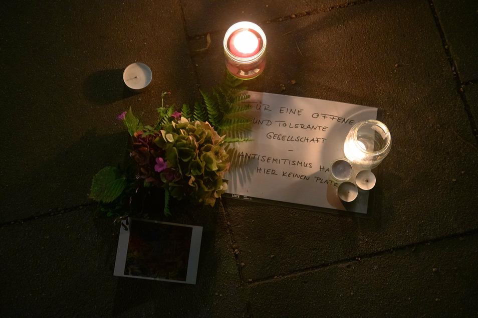 """Ein Schild mit der Aufschrift """"Für eine offene und tolerante Gesellschaft - Antisemitismus hat hier keinen Platz"""" liegt neben Kerzen und Blumen auf dem Gehweg nahe der Synagoge."""