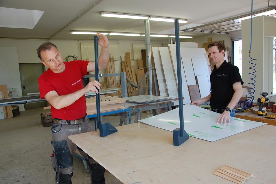 Gerd Baumann (links) und Thomas Kahnt bei der Montage einer Infektionsschutzwand aus Plexiglas.