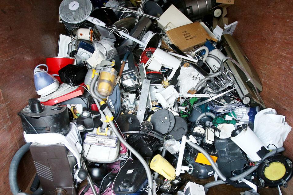 Ausrangierte Haushaltsgeräte und andere Elektrogeräte liegen in einem Sammelbehälter für Elektroschrott.