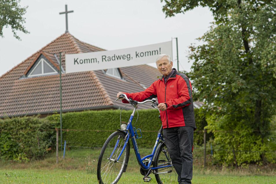 Zwischen Kamenz und Gersdorf klafft noch immer eine Lücke im Radweg. Pastor Wilfried Krause mahnt mit einem Transparent, dass endlich etwas passiert.