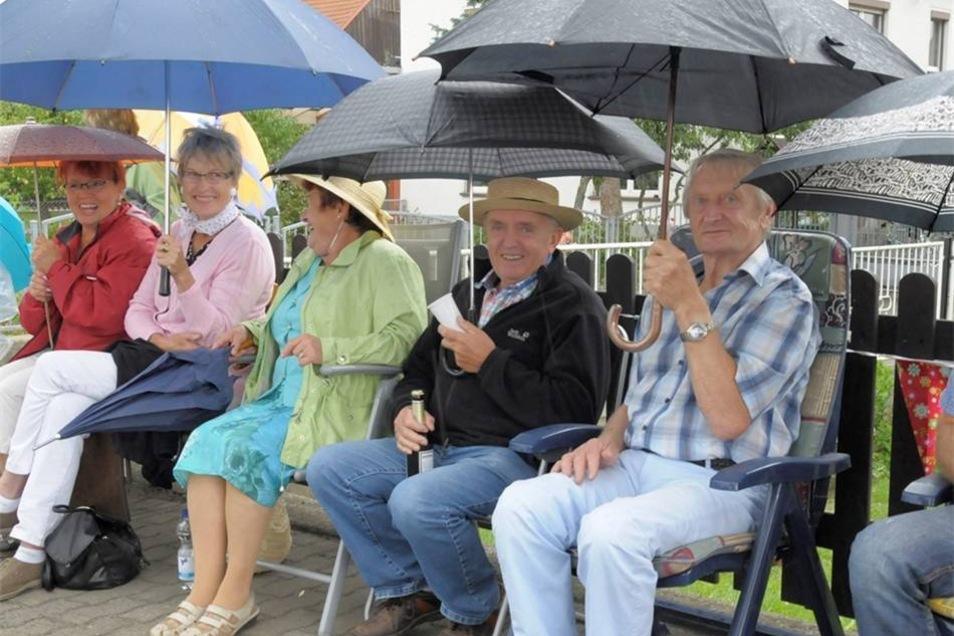 Zuschauer unterm Regenschirm