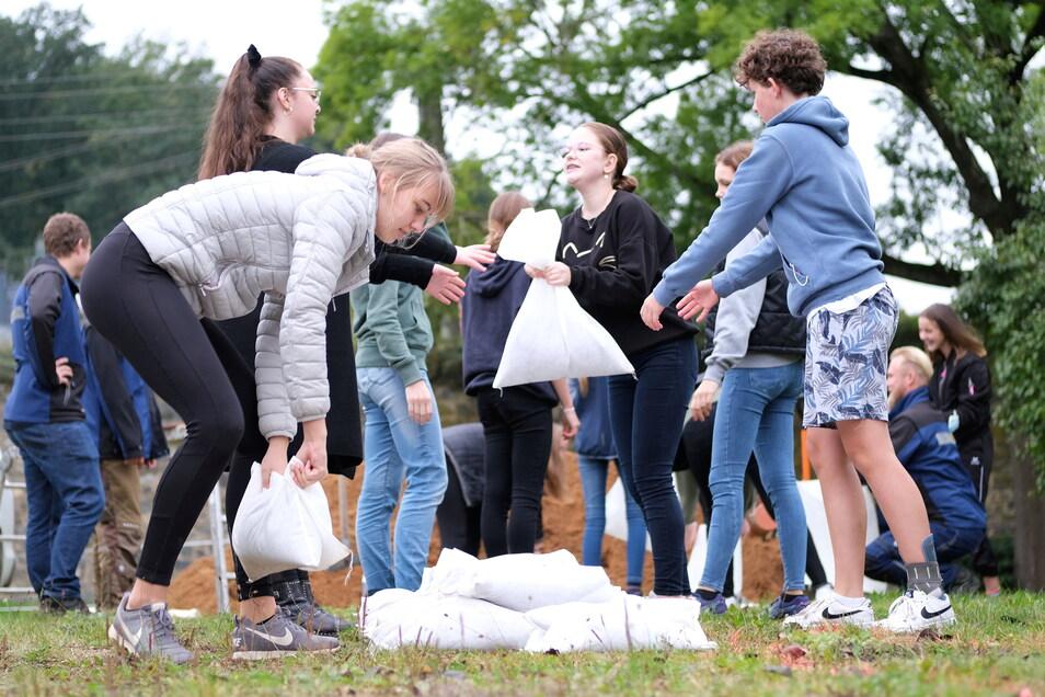 Übung für den Ernstfall. Neuntklässler des Gymnasiums in Nossen lernen, wie bei Hochwasser Sandsäcke richtig gestapelt werden.