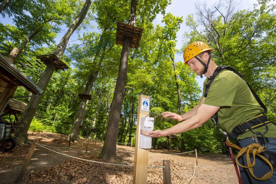 Markus Buttig, Mitarbeiter im Abenteuerpark im Wildgehege Moritzburg, testet einen der neu installierten Spender mit Desinfektionsmittel.