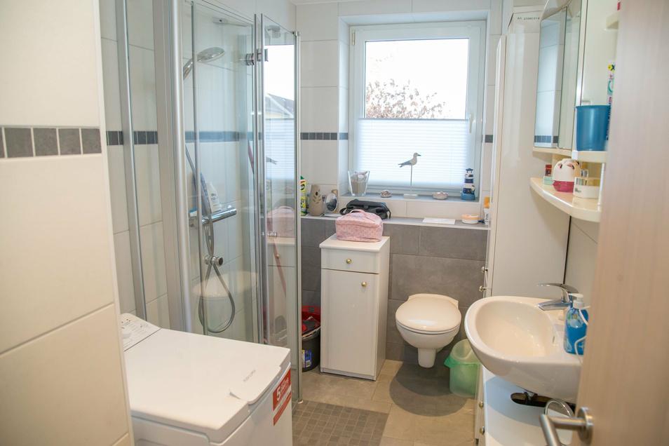 Das Bad ist klein, aber modern und platzsparend eingerichtet. Mit ebenerdiger Dusche und Klappwänden. So hat auch noch die Waschmaschine Platz.