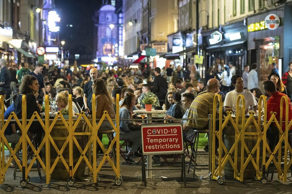 Menschen sitzen hinter einem Zaun im Soho im Londoner West End an Tischen unter freiem Himmel. Angesichts stark steigender Corona-Infektionszahlen in Großbritannien empfehlen Experten offenbar einen weiteren landesweiten Lockdown im Oktober.
