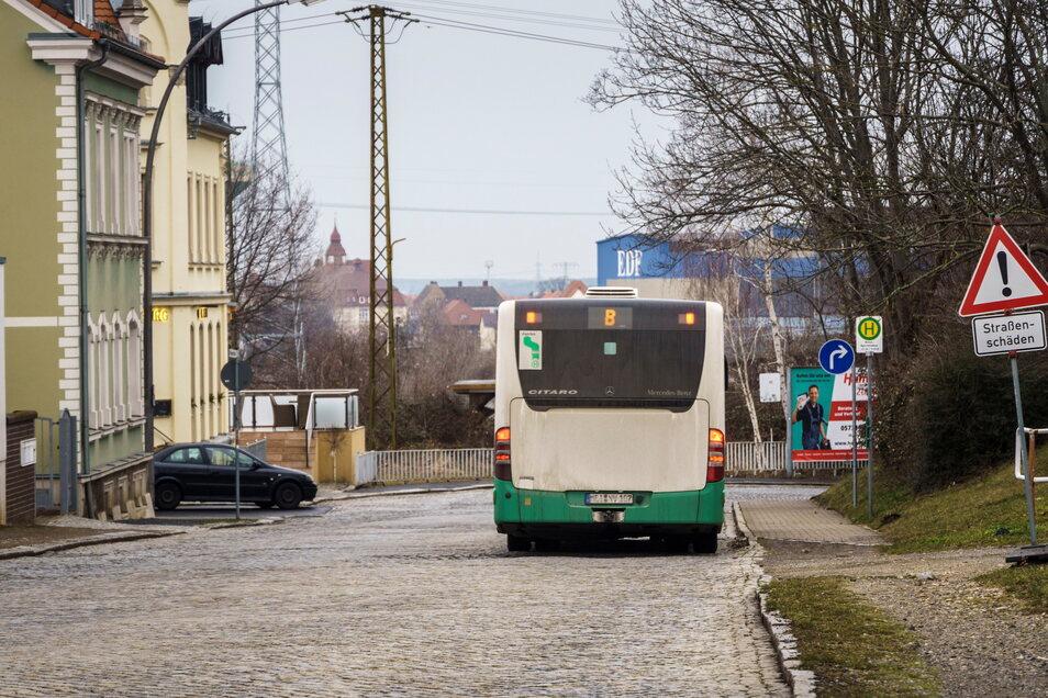 Die Brückenstraße mit dem Bushalt kurz vor der Rechtskurve. Dort geht es zum Bahnhof entlang. Links mündet die Gutenbergstraße ein – eine Einbahnstraße.