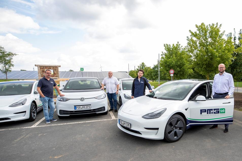 Silvio Michel, René Nowak, Robert Pätzold und David Rriedrich (von links) von der PMG Precision Mechanics Group aus Wilsdruff stehen vor einem kleinen Teil der neuen Fahrzeugflotte mit dem E-Motor.