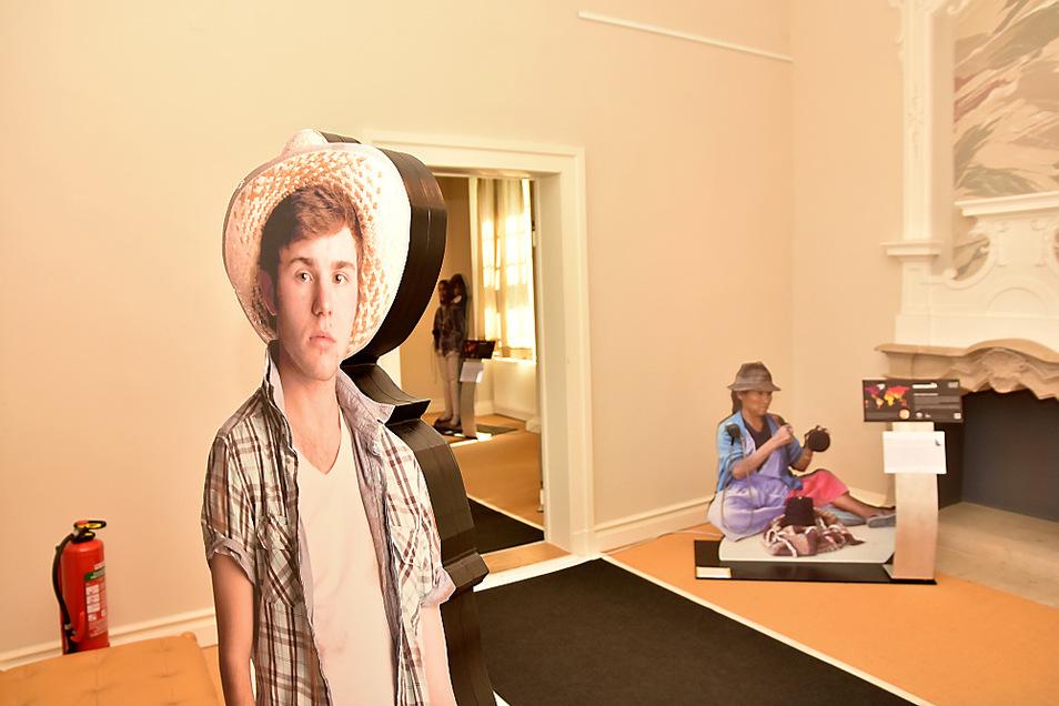 Die Hörstationen der Klimaausstellung sind an lebensgroße Fotos von Menschen angeschlossen: Vorn ein Bauer aus den USA, hinten eine Frau aus Bolivien.