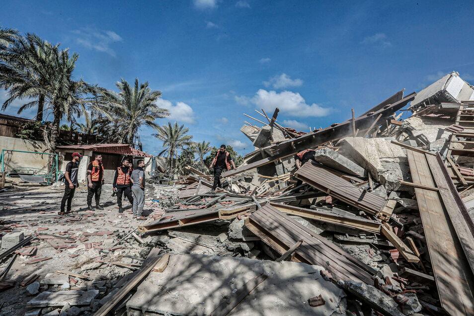 Mitglieder der palästinensischen Zivilverteidigung inspizieren das eingestürzte Wohnhaus, das am frühen Morgen bei einem israelischen Luftangriff zerstört worden ist.